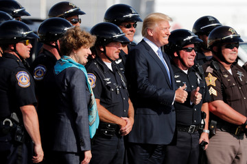 U.S. President Donald Trump poses for a photo with motorcycle police officers before departing aboard Air Force One to return to Washington from Indianapolis International Airport in Indianapolis