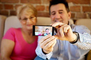 Senior couple making self portrait photo on smartphone