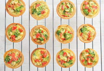 Baking grid with broccoli quiche tartlets on table