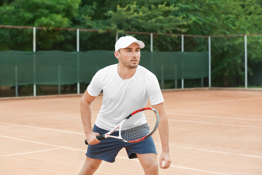 Young man playing tennis on court