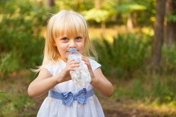 Beautiful little girl drinking water from bottle and smiling outdoors