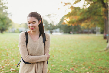 Young mixed race woman - asian & caucasian - standing outside with backpack on fall day
