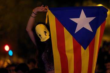 A student wears a mask depicting the cartoon character Tweetie Bird as she waves an  Estelada during a political meeting in favour of the banned October 1 independence referendum in Barcelona