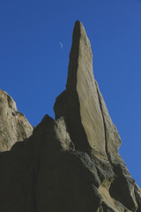 Dramatic rock face against deep blue sky with crescent moon