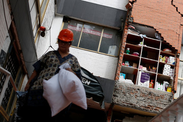 A resident removes her belongings from her damaged apartment after the earthquake, in the Narrate neighborhood in Mexico City