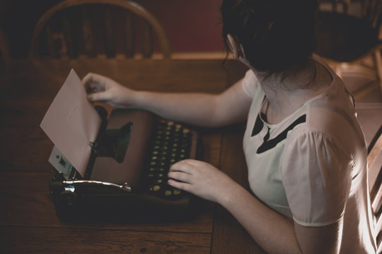 A young woman writes at an old fashioned typewriter