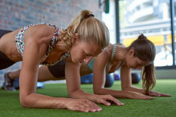 Muscular lean Caucasian women doing push ups exercises planking at urban gym