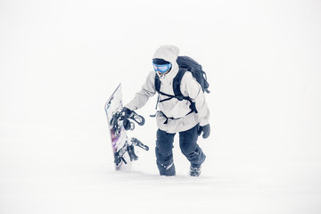 Female snowboarder walking in the snow with snowboard