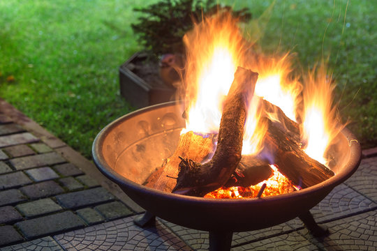 A portable fireplace with bright burning firewoods making sparks and smoke at the backyard  or garden near house. A place for evening meeting and stories