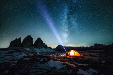 male adventurer with strong headlamp sitting beside illuminated red orange under the milky way at the three peaks