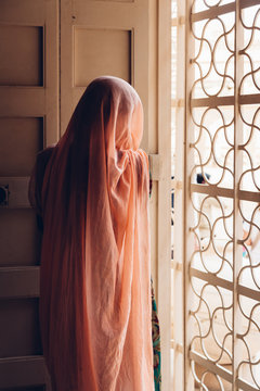 Anonymous women covered in a pale pink sari looking out of a window