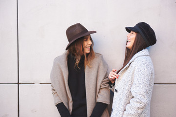 cople of women hanging out against grey wall