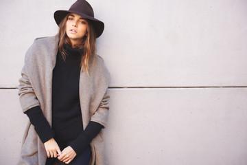 stylish woman against grey wall