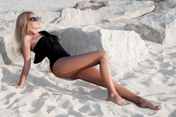 Beautiful tanned woman in black swimsuit on the beach.