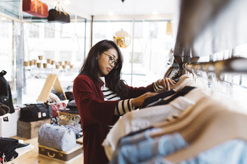 Stylish woman looking through clothing rack at local shop