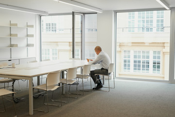 Businessman working alone in boardroom after hours