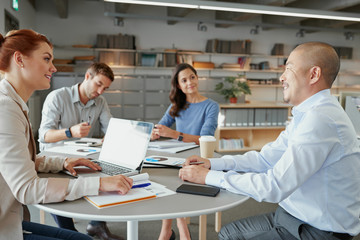 Multiracial team in team meeting sitting at table
