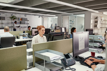 Young redhead business woman using earphones at office workstation
