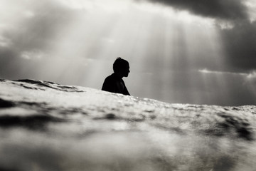 A silhouette of surfer waiting in the lineup with sun rays behind him
