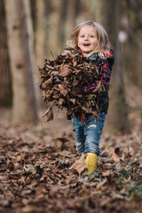 cute smiling little boy with yellow gumboots carrying hands full of leaves ready for a foliage battle