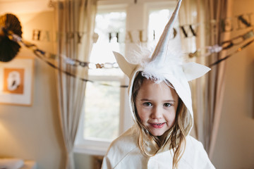 Girl in unicorn costume staring at camera - content