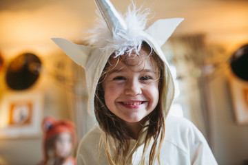 Girl in unicorn costume staring at camera smiling