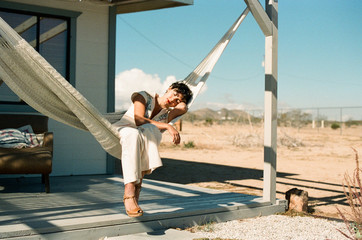 Short hair stylish brunette young woman resting in a Hammock on a porch