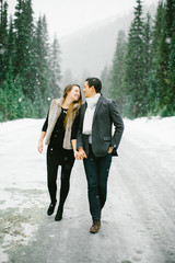 Young engaged couple holding each other in the winter snow.
