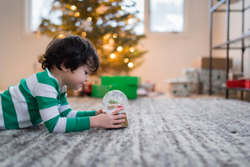 young child with a snow globe in front of a Christmas tree