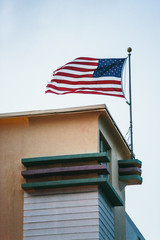 View of a an american flag flying in the wind on top of a building