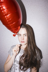 Portrait of attractive young woman holding red balloon and looking at camera