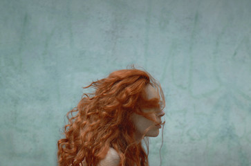 redhead and blue wall with copyspace