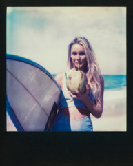 Picture of a Blond Female Surfer Girl Holding Surfboard and Drinking Fresh Coconut