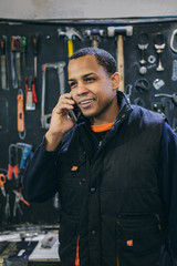 Mechanical Operator Talking by Phone in a Motorbike Workshop