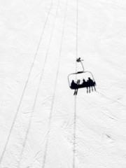 Shadow of three pople riding a chairlift on a groomed ski slope