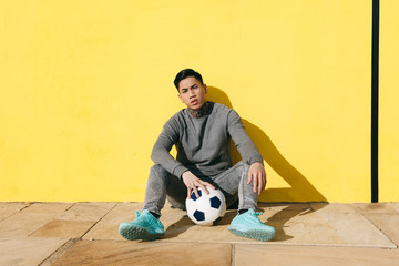 Asian tattooed man sitting with soccer ball in front of a yellow wall.
