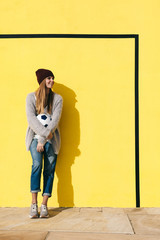 Young woman holding soccer ball in front of a yellow wall.
