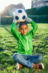 Portrait of a kid holding a soccer ball sitting on grass.