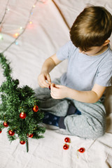 Male kid decorating a christmas tree, from above, vertical