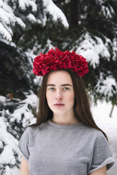 Attractive young woman wearing red wreath made of faux flowers