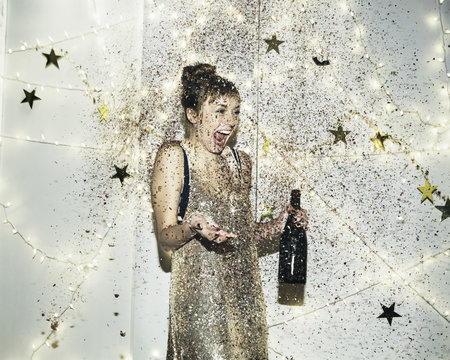 Young woman being showered in glitter