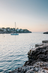 A yacht anchored off the coast in a cove at sunrise