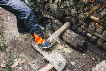 lumberjack chopping wood in a forest with an electric saw