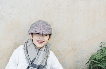 Boy laughing at camera with his cap almost covering his eyes