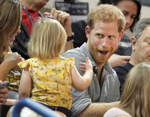Britain's Prince Harry, patron of the Invictus Games Foundation, shares popcorn with a child while attending the Sitting Volleyball competition at the games in Toronto
