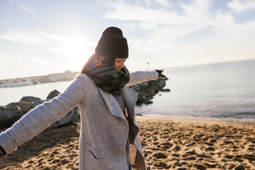 Chinese woman enjoying a sunny winter day on the beach.