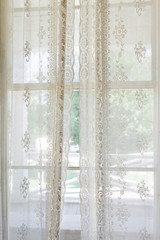 Delicate lace curtains covering a window in summer