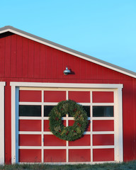 Christmas wreath on door of red barn