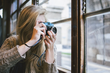 Young woman using a film camera on the tram