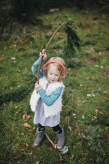 Little Girl Stands with a Large Pine Branch Over her Head